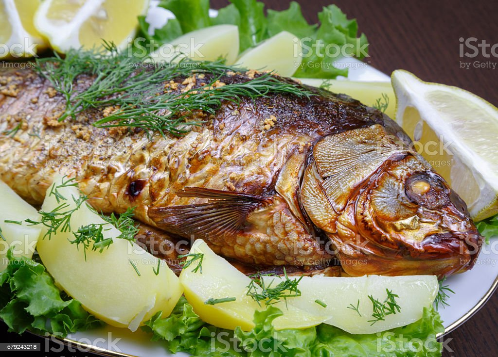 Carp cooked in the oven with potatoes and lemon stock photo