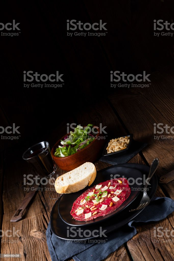 Carpaccio of beef with pine nuts, colorful pepper and Parmesan cheese royalty-free stock photo