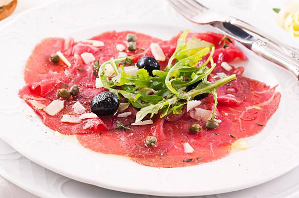 carpaccio mit oliven und parmesan - carpaccio salat stock-fotos und bilder