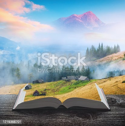 Carpathian misty mountains with old rustic houses on the pages of an open magical book. Majestic landscape. Travel and education concept.