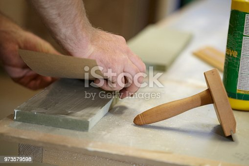 A carpenter veneers, glues and clamps a piece of wood in his workshop.
