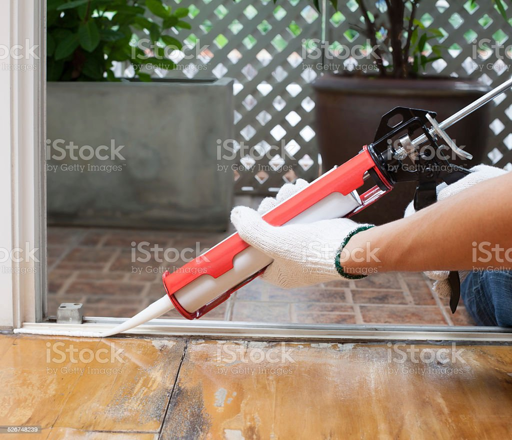 Carpenter applies silicone on the wooden floor stock photo