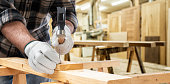 Close-up. Carpenter with his hands protected by gloves with hammer and nails fixes a wooden board. Construction industry, carpentry workshop.