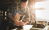istock Carpenter at workshop polishes wooden board with a electric orbital sander 1214255355