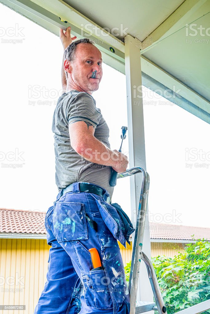Carpenter building a porch, home Construction. Image of a builder. stock photo