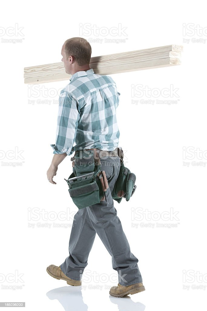 Carpenter carrying wooden planks on his shoulders stock photo
