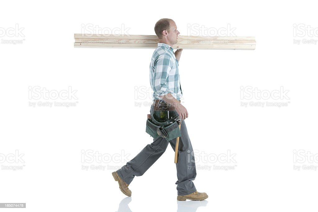 Carpenter carrying wooden planks stock photo