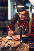 Close-up image of senior artist working on decorative wooden plate