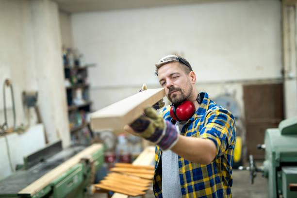 tischler überprüfen die qualität des holzmöbelteils. - waldhandwerk stock-fotos und bilder