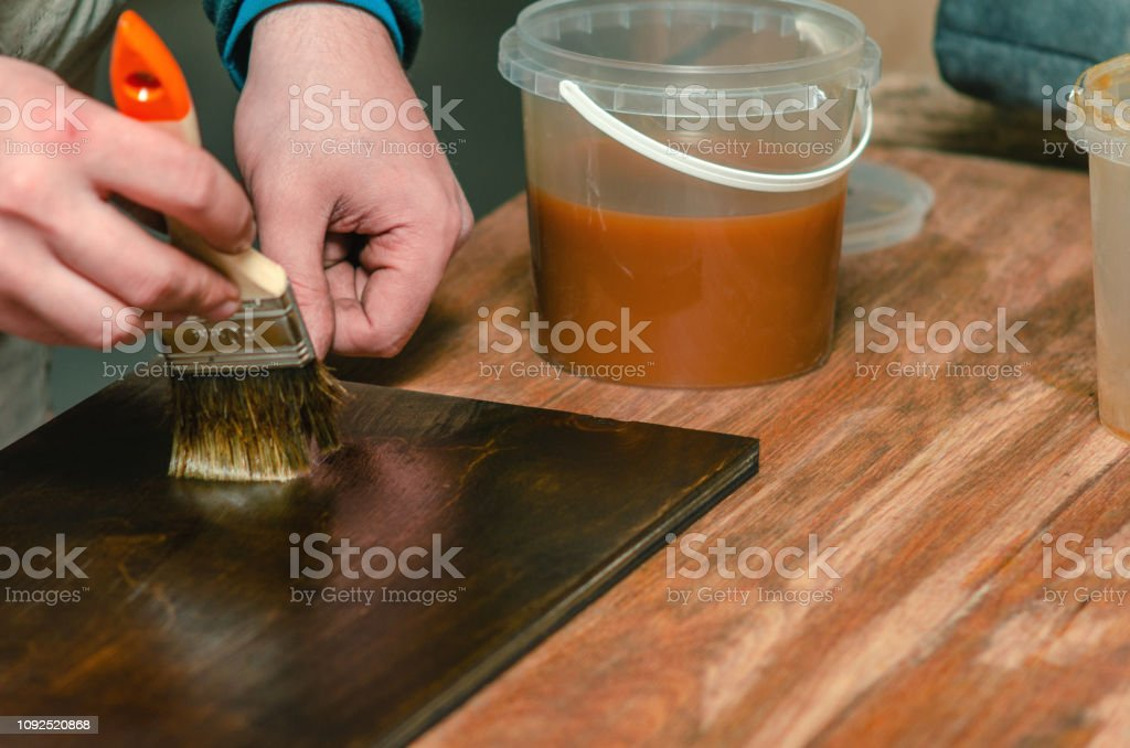 Carpenter paints tinted wood furniture details with wax for wood...