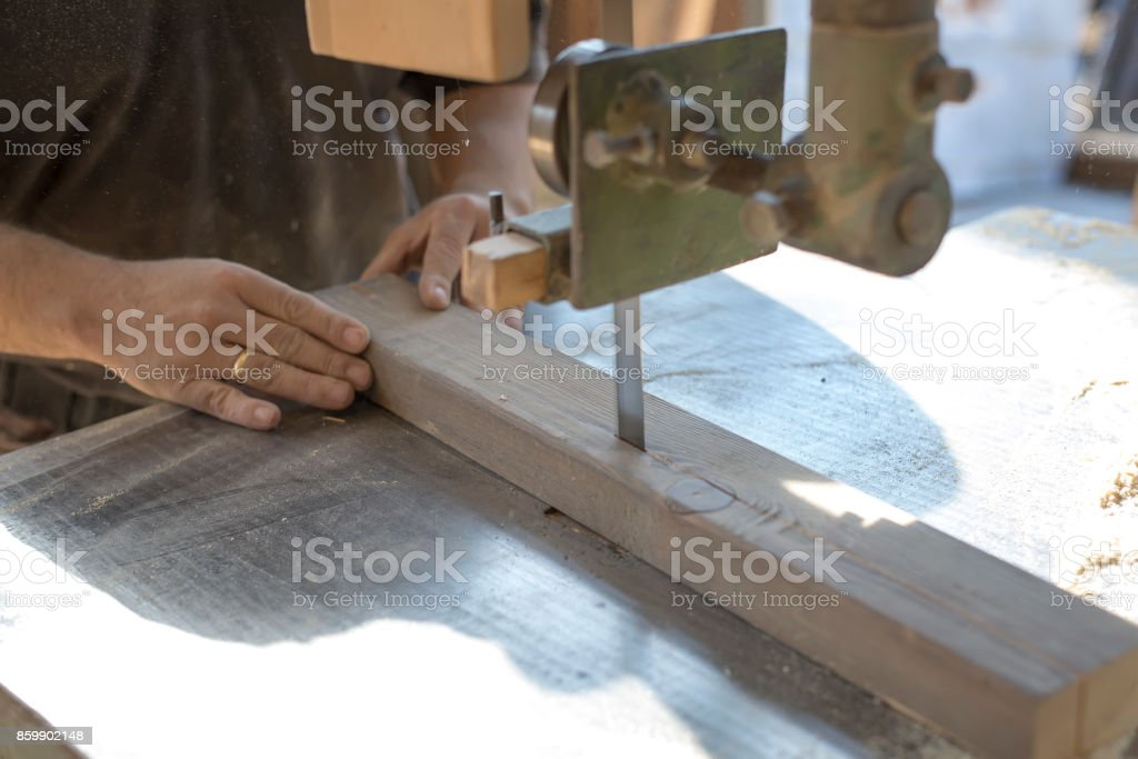 A carpenter cuts a board with a band saw. stock photo