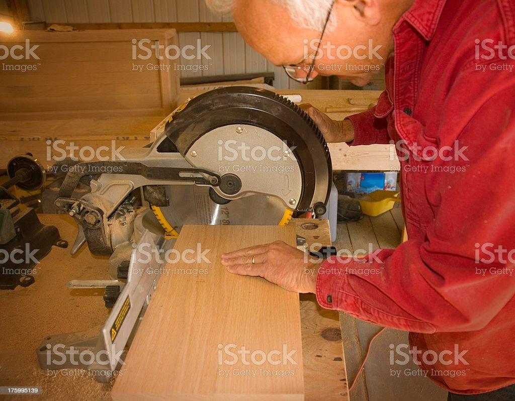 Carpenter Cutting a board stock photo