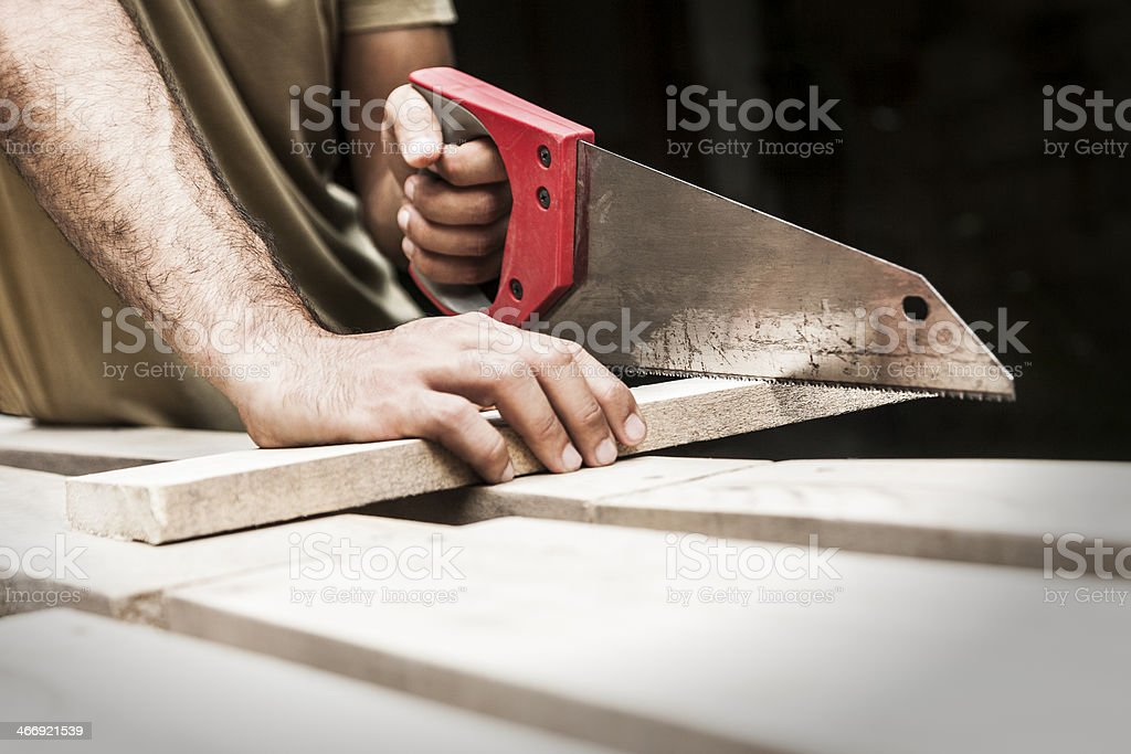 Carpenter cutting board with saw closeup royalty-free stock photo
