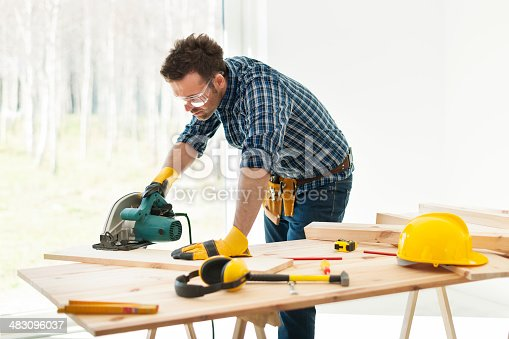 istock Carpenter cutting plank by circular saw 483096037