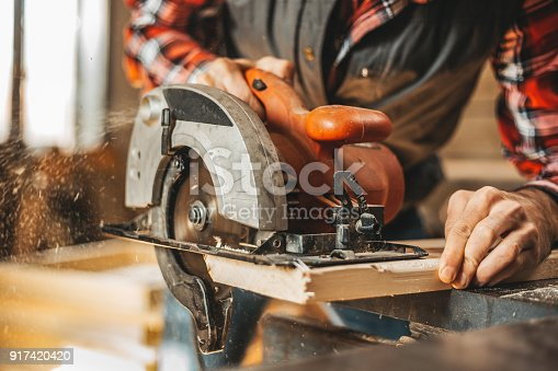 istock Carpenter cutting plank by circular saw 917420420