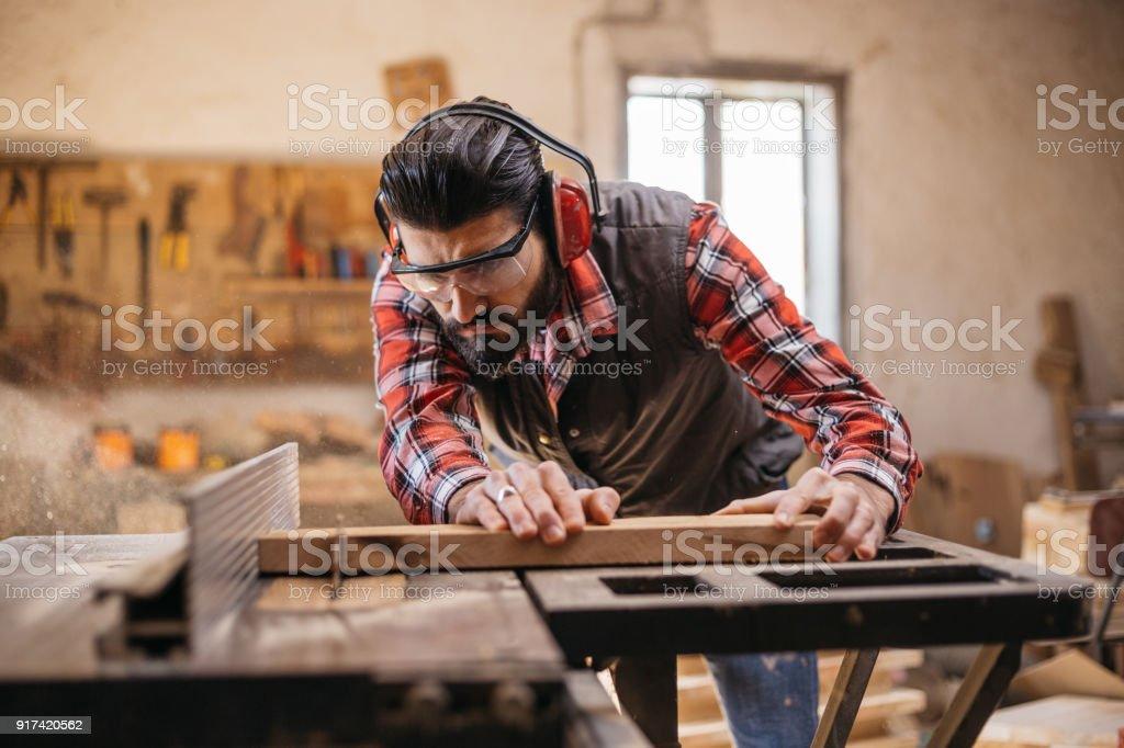 Carpenter cutting plank by circular saw stock photo