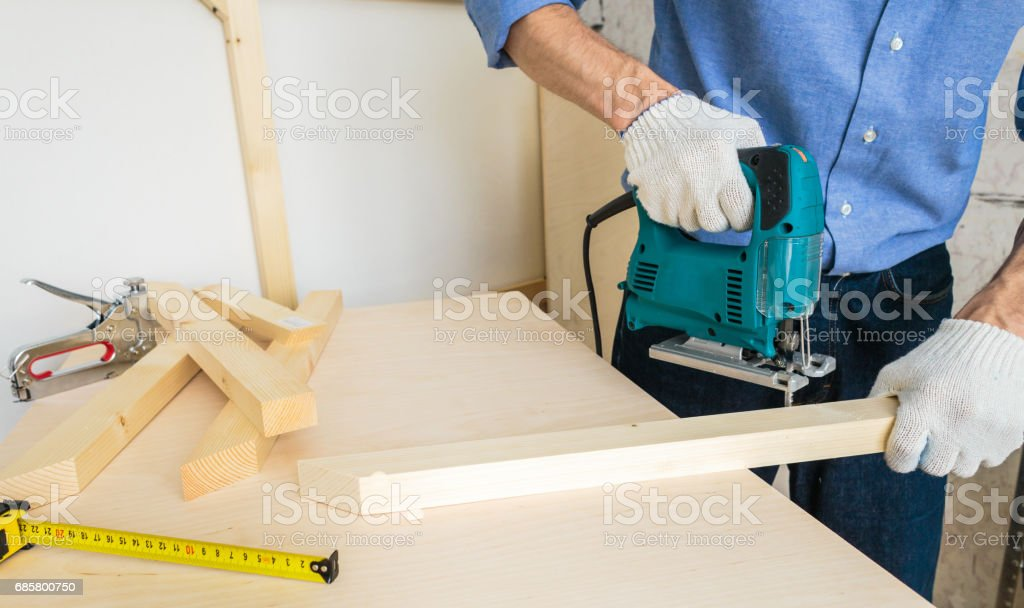 Carpenter Cutting Wood Stack, Hands Hold Power Tool stock photo