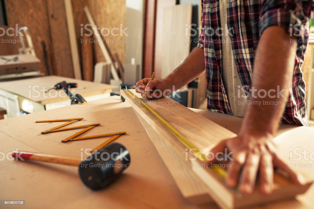 Carpenter doing his job in carpentry workshop. stock photo