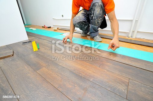 istock Carpenter doing laminate floor work 586381478