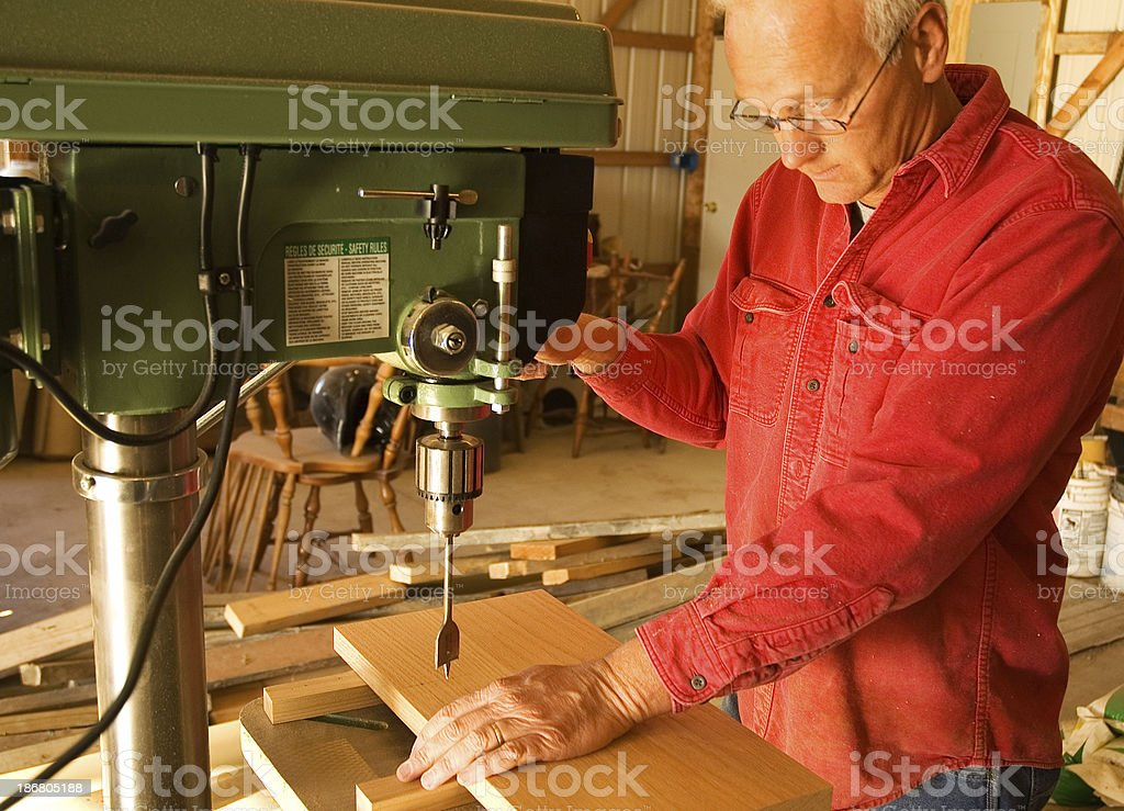 Carpenter drilling a hole stock photo