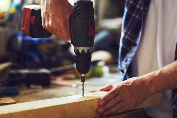 Carpintero perfora un agujero con un taladro eléctrico en una tabla de madera - foto de stock
