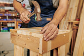 Hands of carpenter driving nail in wooden stool with hammer
