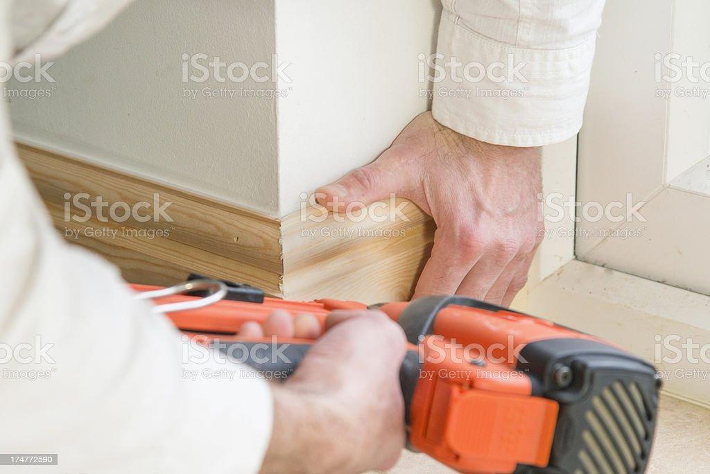 Carpenter fitting base board or skirting with a nail gun stock photo