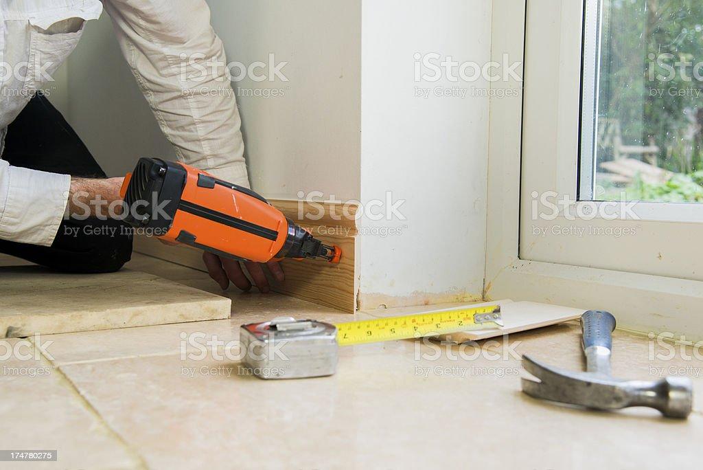 Carpenter fitting base or skirting board with a nail gun stock photo