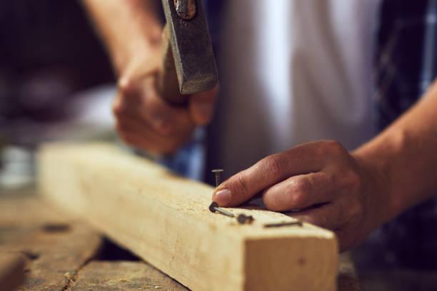 Martillar un clavo en un tablón de madera en su taller de carpintero - foto de stock