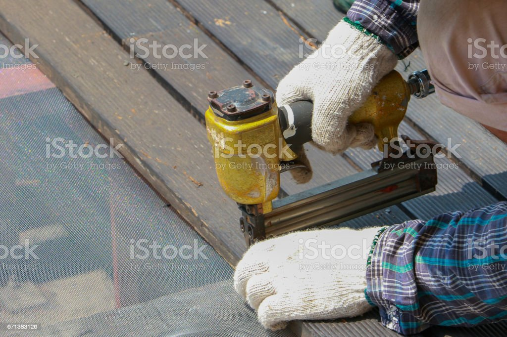 Carpenter hand or hand of worker drills a hole with wooden plank using air nailer machine. stock photo