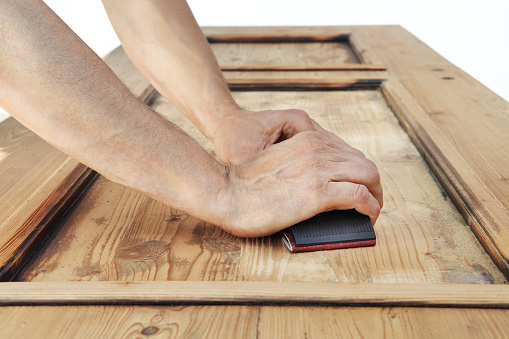 1015564946 istock photo carpenter hands work the wood with the sandpaper 968260136