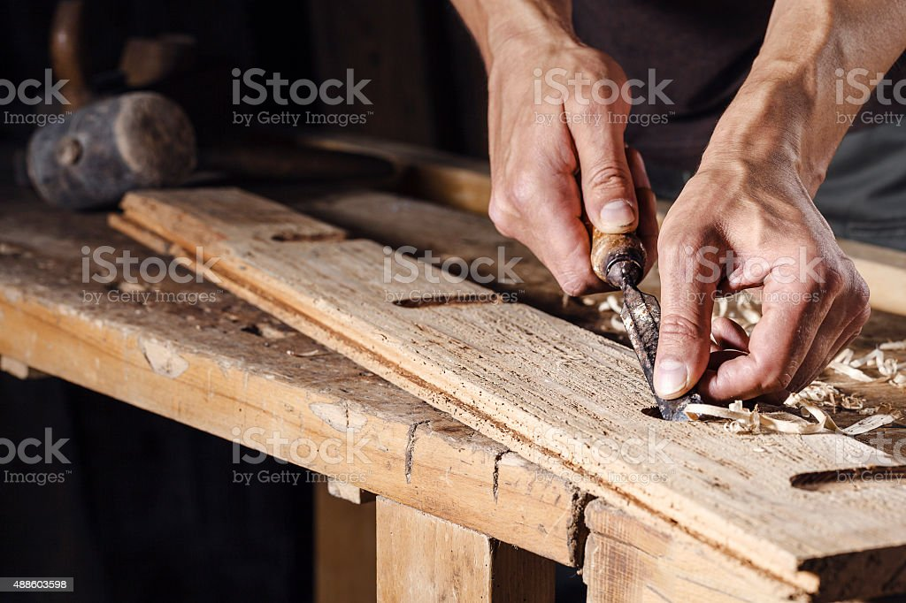 carpenter hands working with a chisel and carving tools stock photo