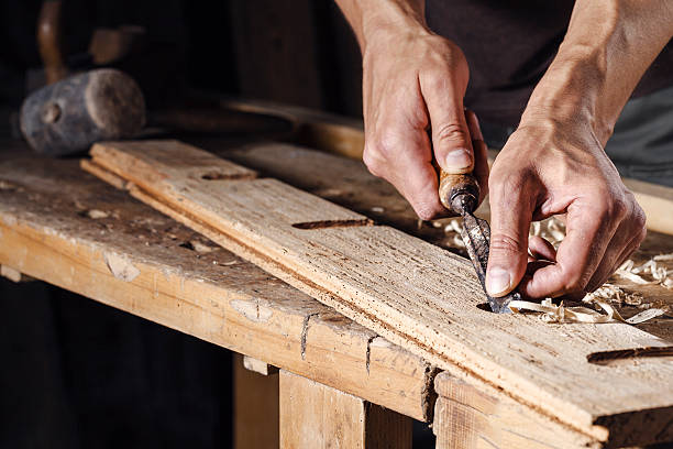 carpenter hands working with a chisel and carving tools Closeup of a carpenter hands working with a chisel and carving tools on wooden workbench carving craft product stock pictures, royalty-free photos & images