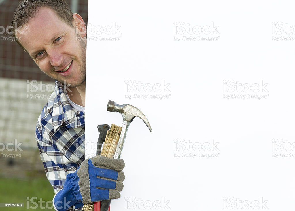 Carpenter holding tools and billboard royalty-free stock photo