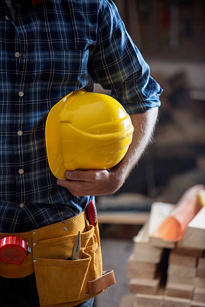 Carpenter  holding yellow hemlet stock photo