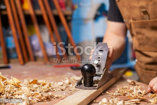 Carpenter in an apron planing a wooden board with a planer, workplace.