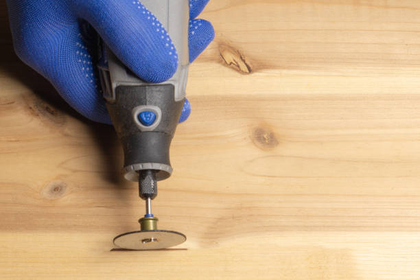 carpenter in blue protective gloves handles wooden dremel - dremel wood stock photos and pictures