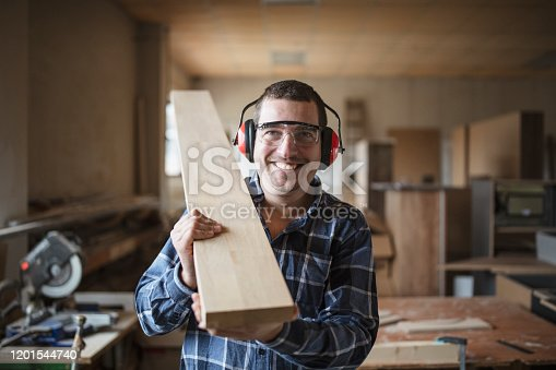 Smiling carpenter holding a wooden beam in workshop, wearing ear muffs and protective goggles, he smiling and looking at camera.
