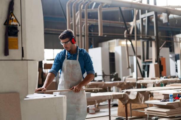 Carpenter inserting wood in machine at factory stock photo