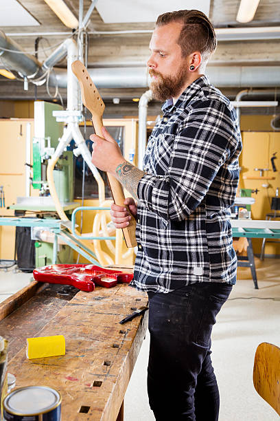 carpenter inspects a wooden guitar neck in workshop - baroque tattoo stock-fotos und bilder