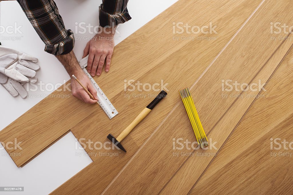 Carpenter installing a wooden flooring stock photo