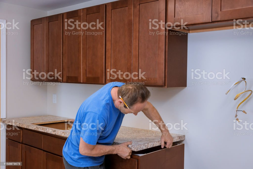 Carpenter Installing C Counter Top In A Kitchen Stock Photo Download Image Now Istock