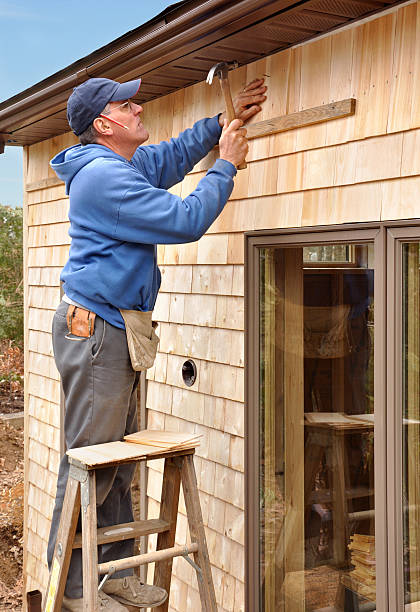 Carpenter installing cedar shingles stock photo