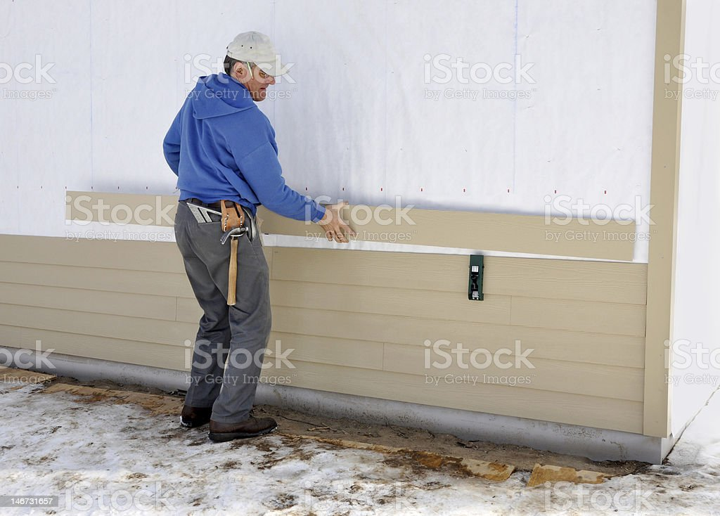 Carpenter installing siding royalty-free stock photo