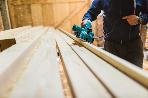 istock Carpenter is planing a wooden plank 1084249050
