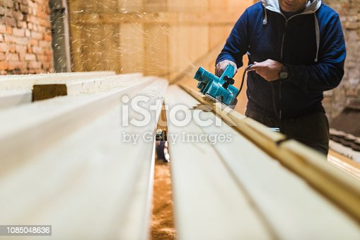 Carpenter is planing a wooden plank