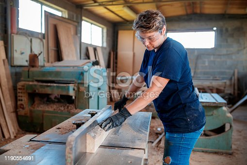 Mid adult female carpenter is planing a wooden plank