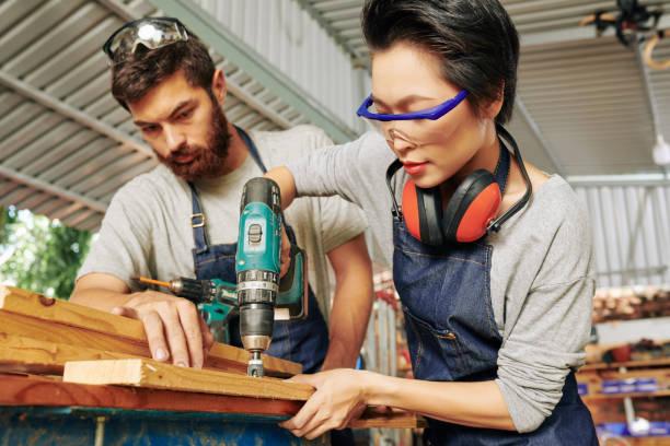 Carpintero mirando a la perforación compañero de trabajo - foto de stock