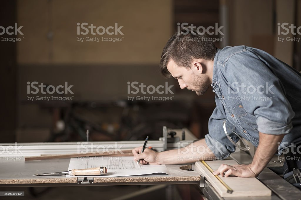 Carpenter looking at the plans stock photo