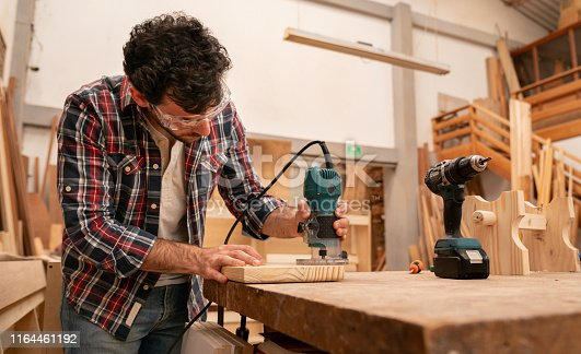 Carpenter making a piece of furniture and using a router at his wood workshop